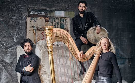 dorience marselje sitting to the right of her harp with one musician on the left of the harp and the other above her.