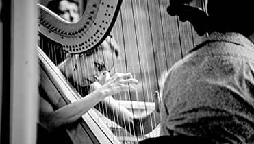 black and white shot of Doriene Marselje close up playing harp.