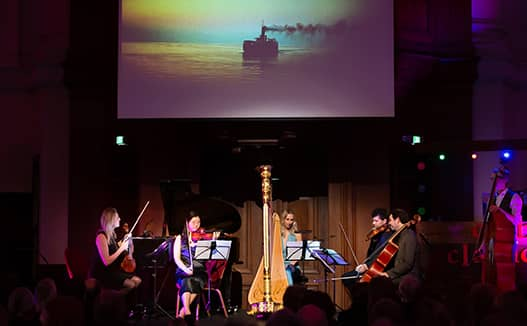 4 musicians playing with doriene on spot light stage. Projector of ship on the sea in the background.