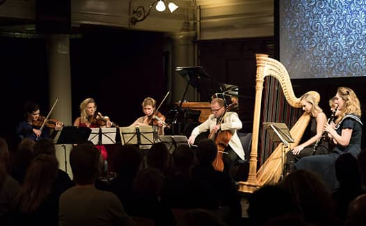 doriene playing harp on the right with 4 musician on the left. Projector showing organic patter in the background.