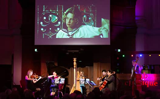 4 musicians playing with doriene on spot light stage. Projector of woman in the background