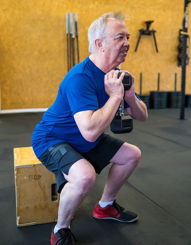 Pat squatting to a box whilst in a personal training session