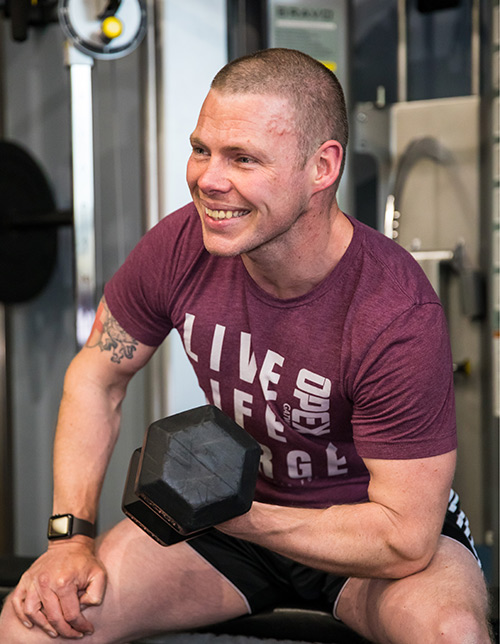 Client curling dumbbell in the gym whilst smiling