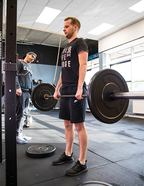 Client deadlifting in the gym whilst being coached by a personal trainer