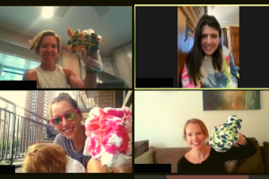 four people on zoom holding up their tie dye shirts