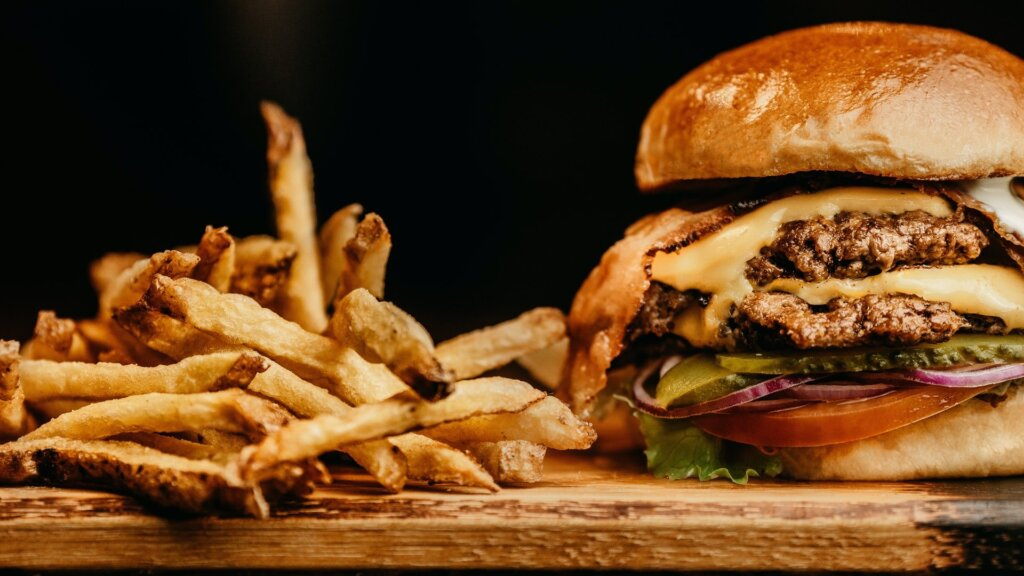 Burger and fries on table. A popular design niche