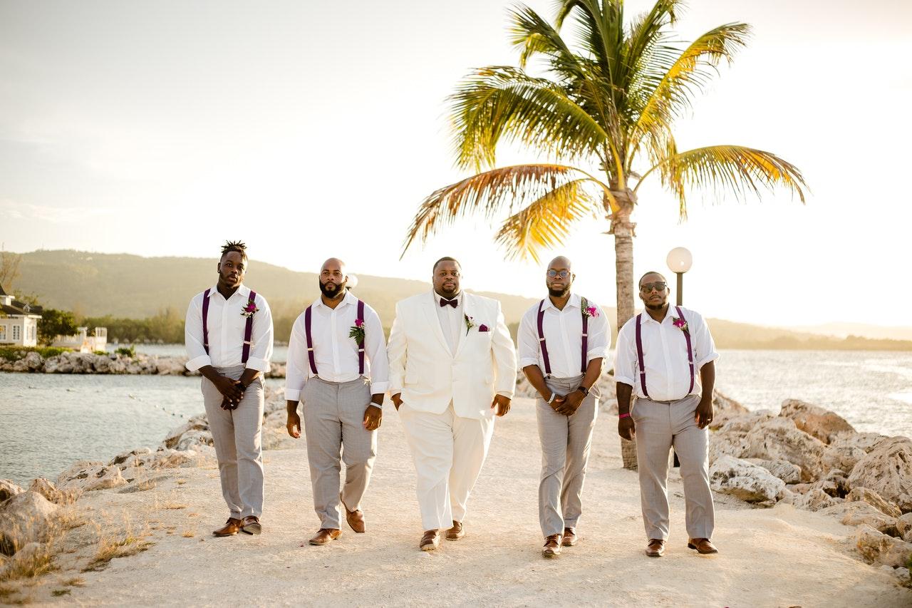 Black groom and groomsmen walking on beach