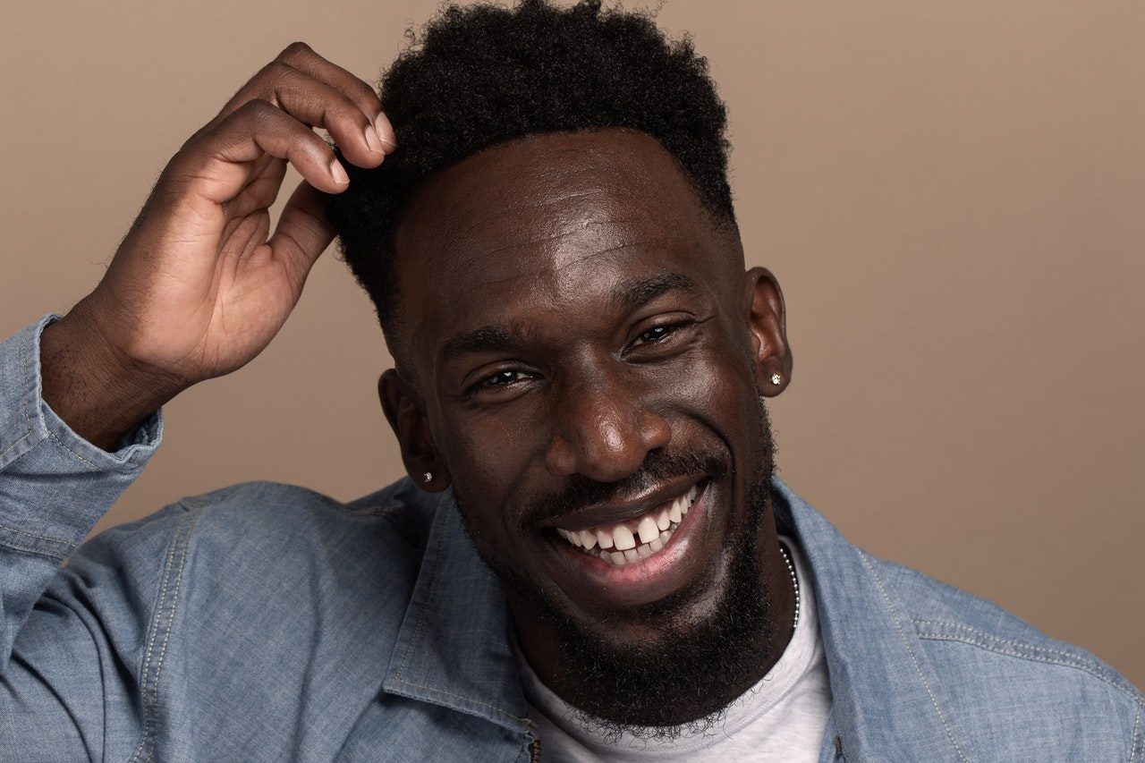 Portrait of handsome Black man smiling while playing with his hair