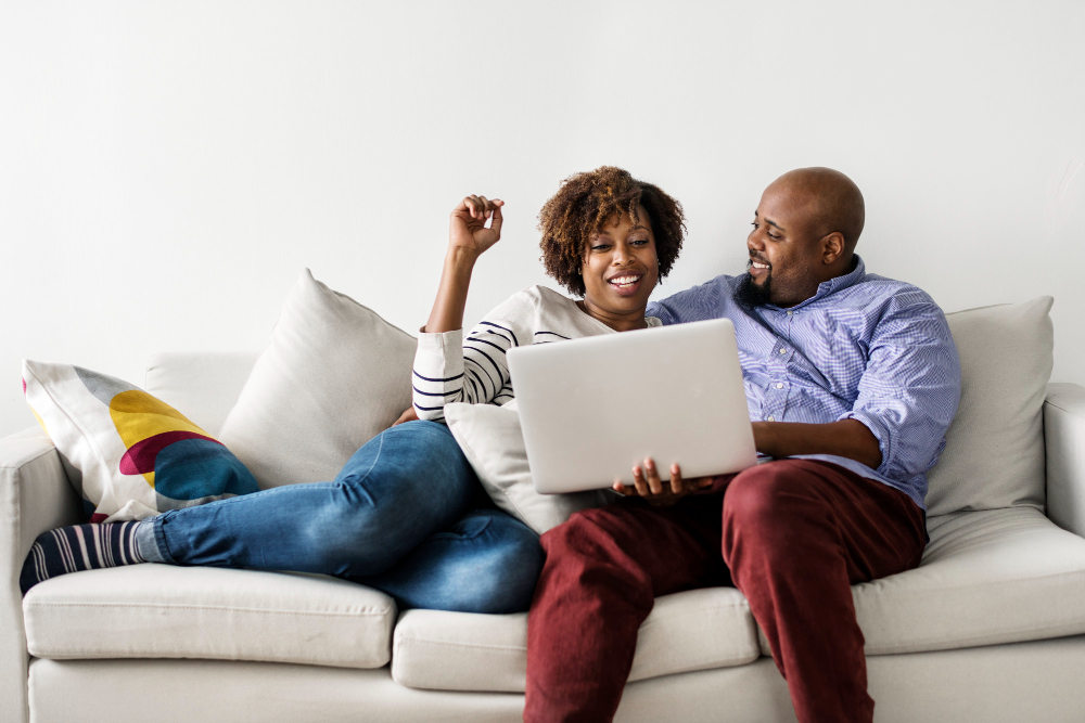 African american couple sitting on sofa and smiling