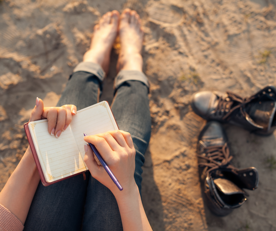 Image of a woman sitting on the beach with her feet in the sand writing in a journal, shot from behind and above her head.