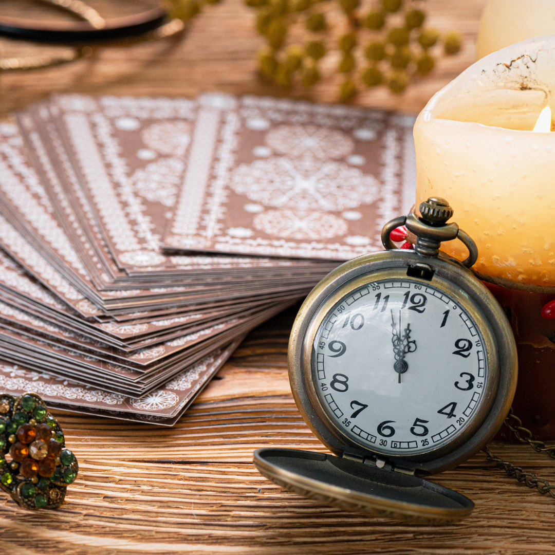 Image of a pocket watch leaning on a deck of tarot cards, and a lit candle on the top of a wooden desk.