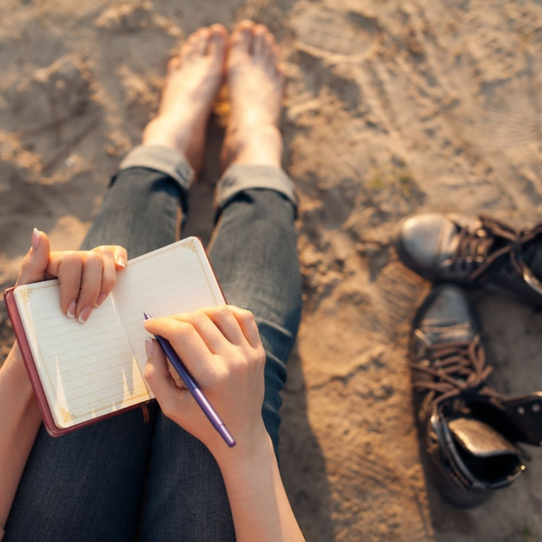 first person perspective of looking down at a journal page getting to write while sitting barefoot on a sandy beach.