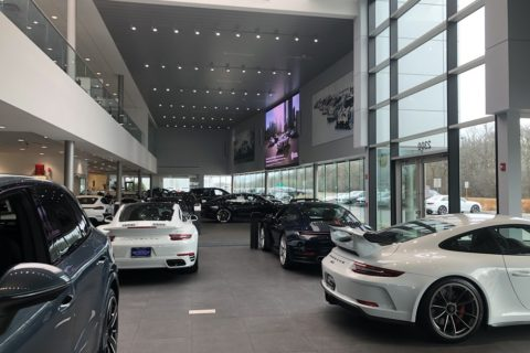 Cars in dealer-room with big TV.