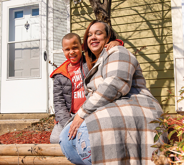Photo of LaShawn R. and her son outside of a yellow house