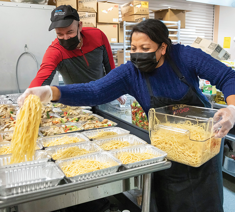 Photo of a man and woman preparing meals for delivery