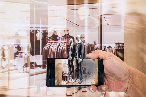 two digital avatars coming out of a smartphone sacanning a fashion store