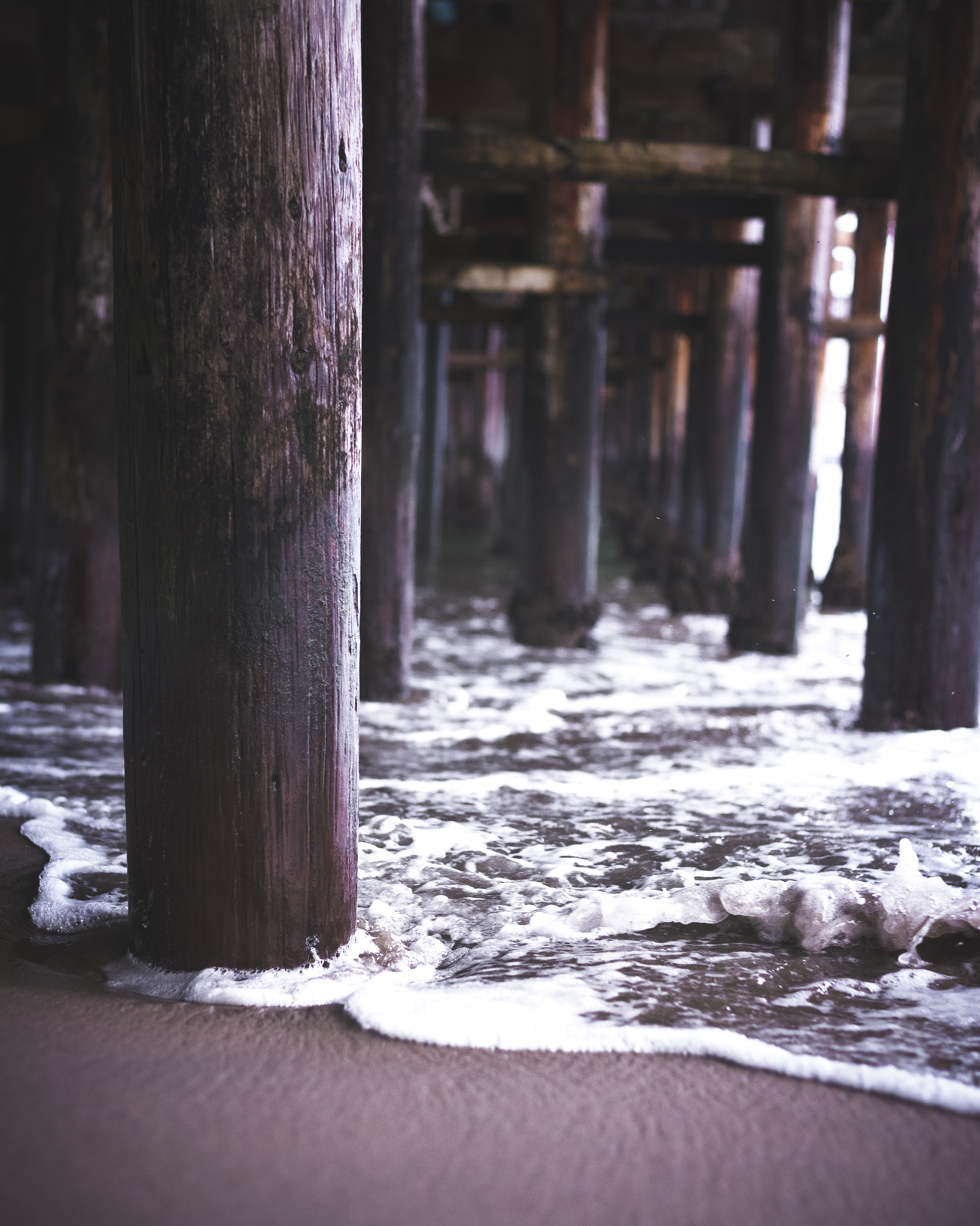 Seaside pier legs reaching down to the sand with whiete water waves washing around them