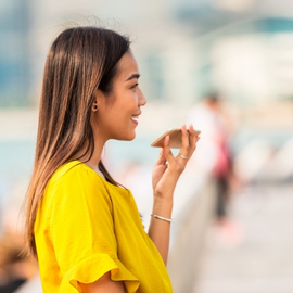VoLTE. A woman with a bright yellow blouse talking to a mobile phone in the street.