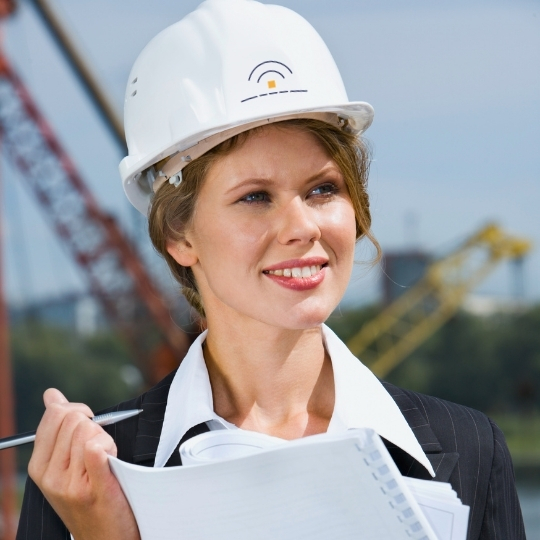 Network consultant on site. Blond woman in a suit holding a pen in her hands. She's wearing a helmet with Omnitele favicon