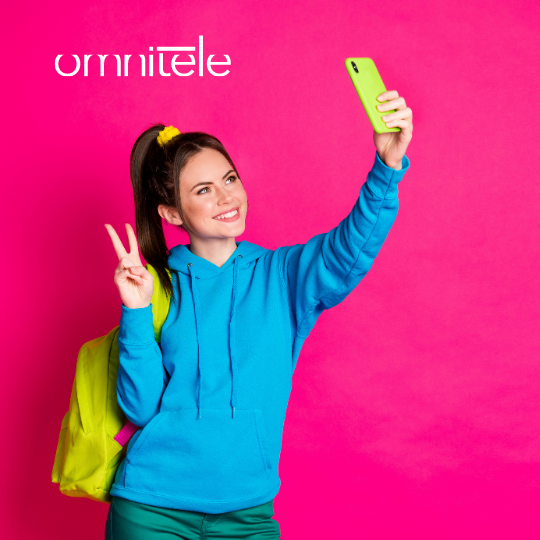 Girl with a blue hoodie holding a yellow phone taking a selfie. Pink background and Omnitele logo in white