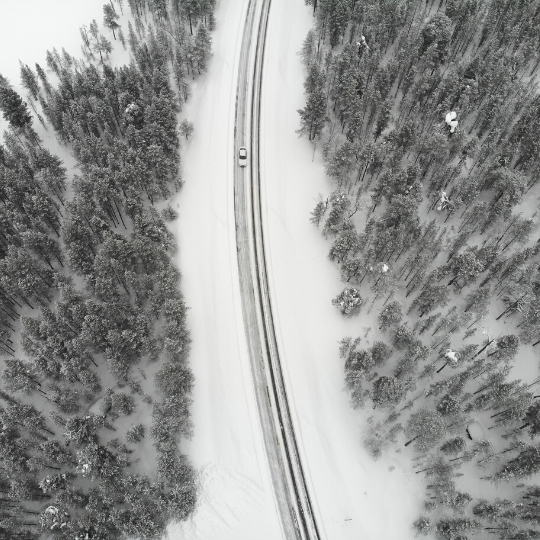 Mobile drive testing in Finland during winter. Forest during winter and a white car driving on the road.