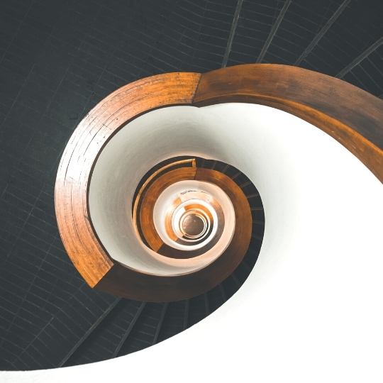Network cost reduction. Architecture. Classic black spiral stairs with a brown handle and white paint on the inside.