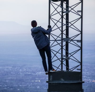 Re-evaluating 5G strategies. A man in a 5G antenna, looking at the city.