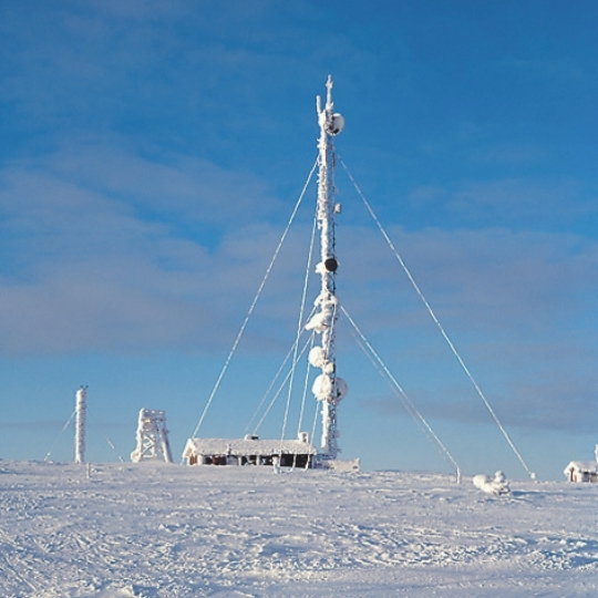 5G antenna covered with snow in a sunny winter day