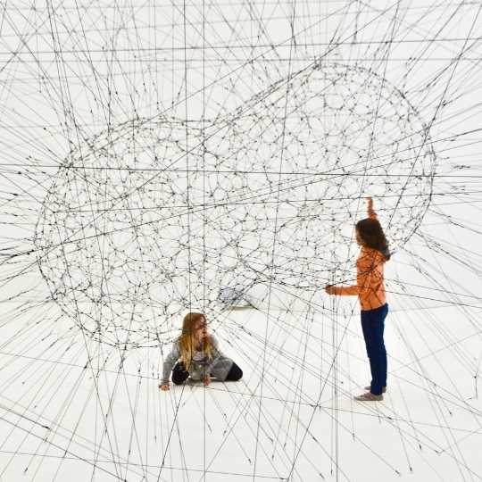 Feasibility studies. Two girls in a museum holding a net that represents technology studies.