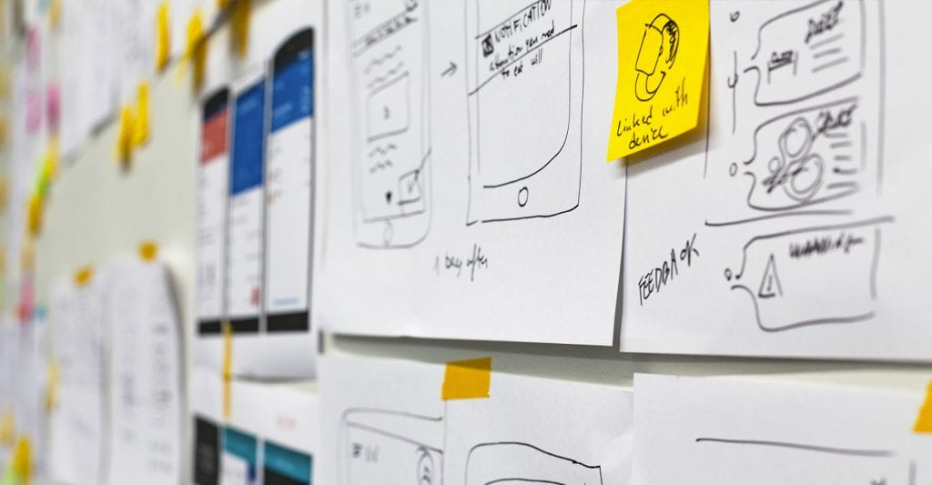 Whiteboard with wireframes and sticky notes