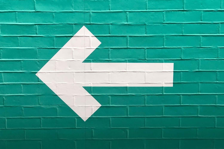 White arrow on green brick, pointing left