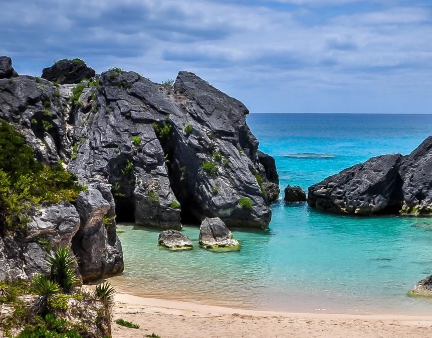 View of a cove from the land, with white sand and turquoise water, surrounded by some rocks
