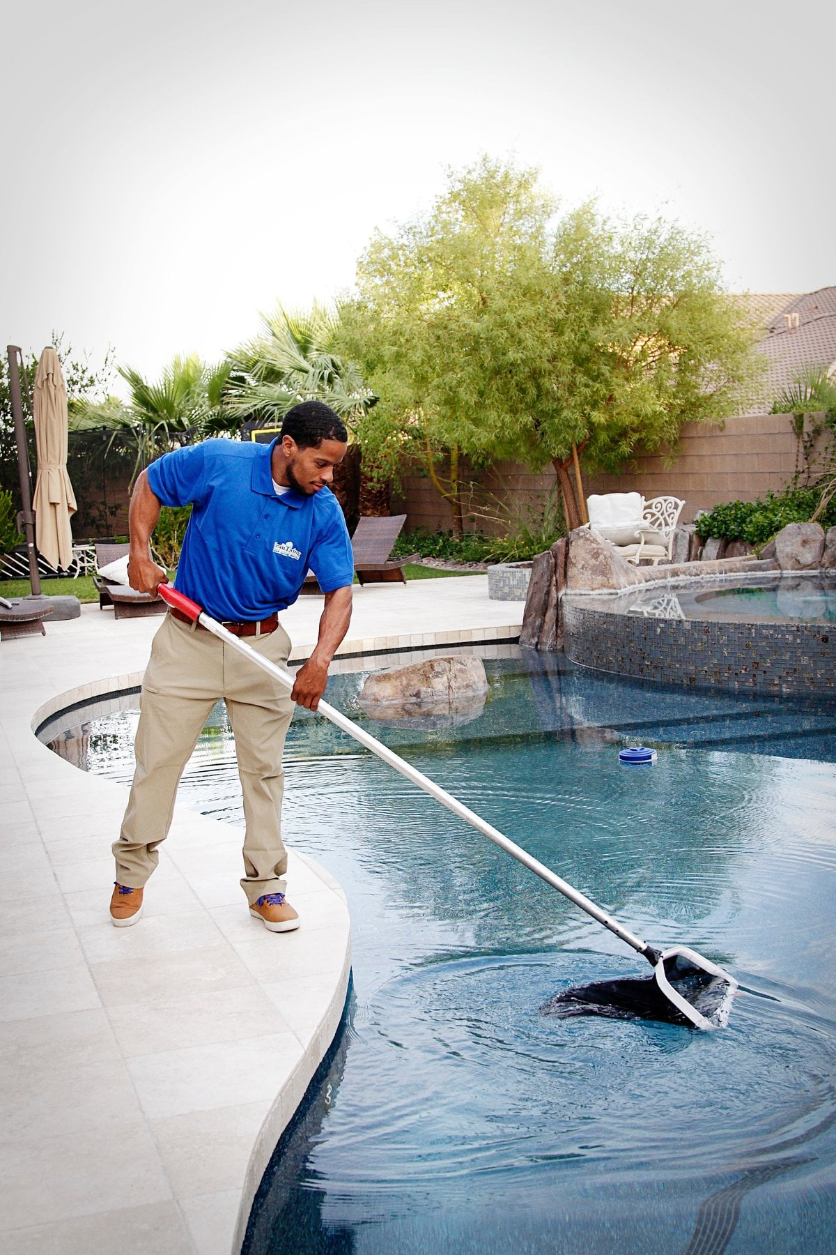 Pool guy cleaning pool