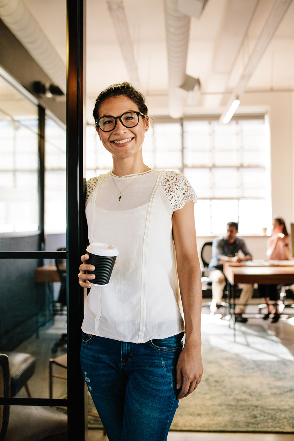Woman smiling holding a coffee in a modern office