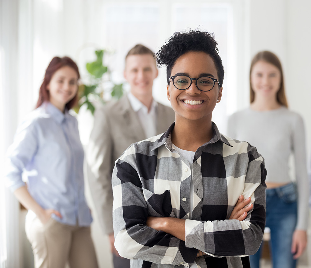 A woman smiling in the foreground while her coworkers smile in the background - out of focus