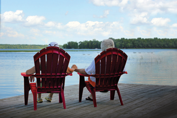 Couple sitting on red Adirondack chairs looking out over Leech Lake