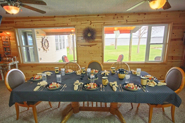 The large dining table set for breakfast on a beautiful day on Leech Lake.