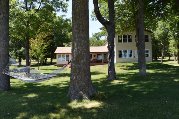 A view of the B&B through the trees in the front lawn by the lake.