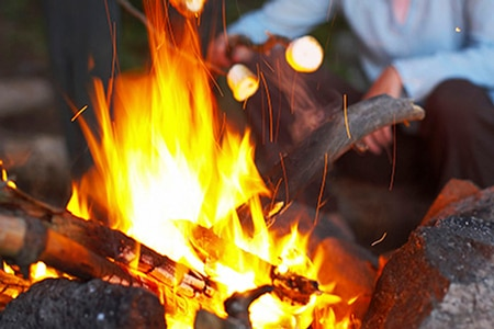 Roasting marshmallows over a fire.