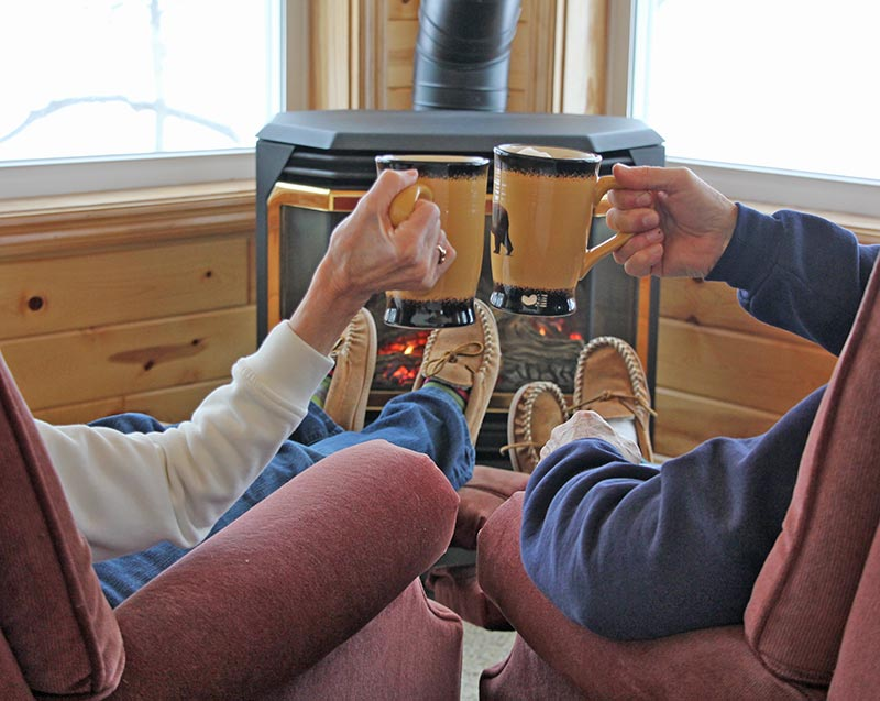 Couple relaxing by a cozy, romantic fire with mugs of cocoa in the Bay View Suite.