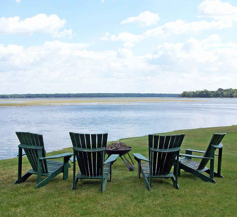 Adirondack chairs around the fire pit on the shores of Leech Lake