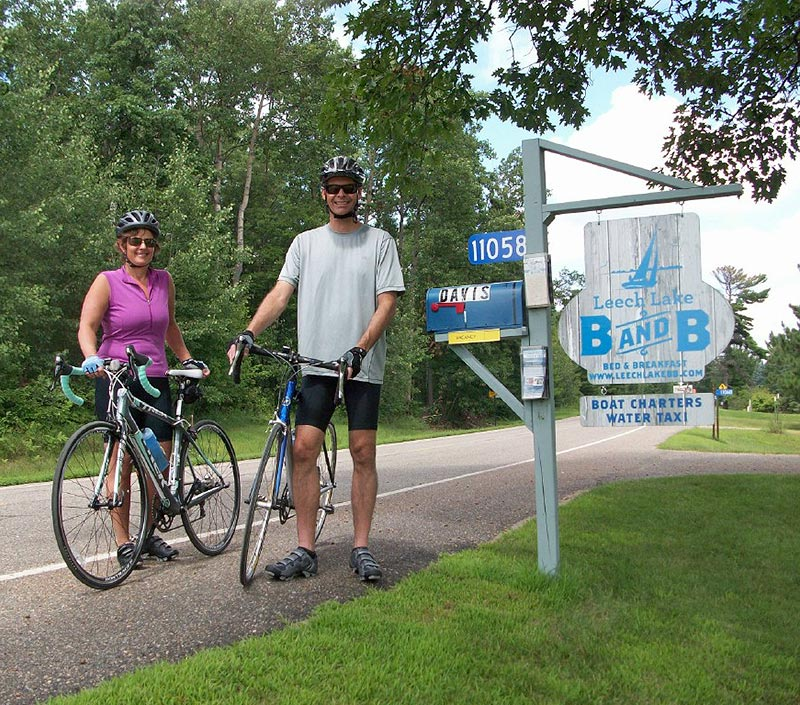 Couple with their bikes at the Leech Lake B&B sign