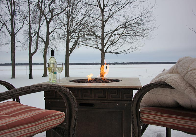 The fire table on the deck overlooking the lake in winter.