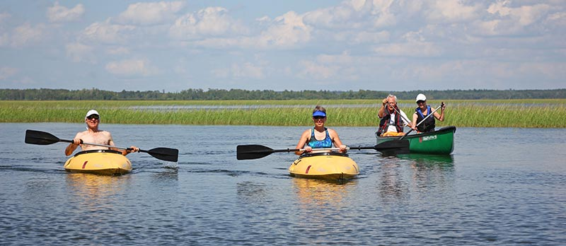 People canoeing and kayaking on Leech Lake on a beautiful sunny day.
