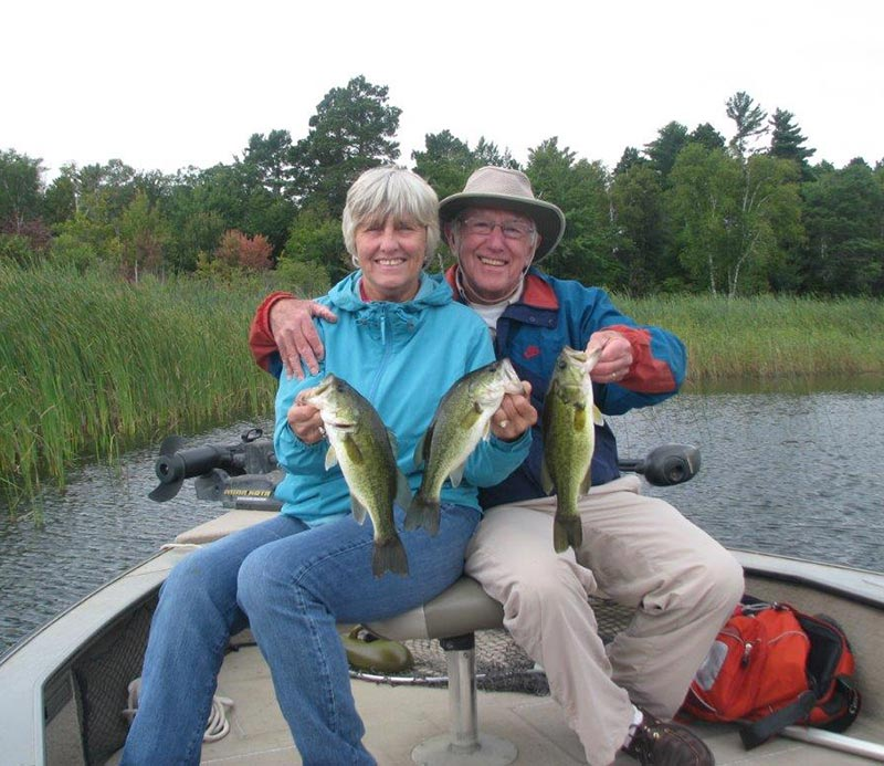 A couple in their fishing boat holding up the bass they caught on Leech Lake