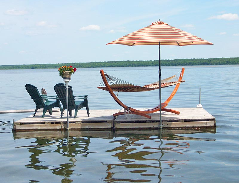 Hammock with umbrella and Adirondack chairs on the floating dock