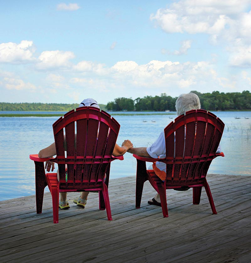 Couple sitting holding hands in red Adirondack chairs on the lake