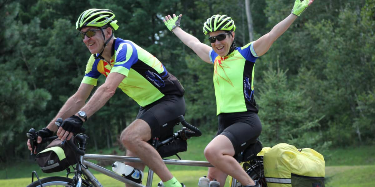 Riding the tandem bike with backseat rider holding hands up in the air