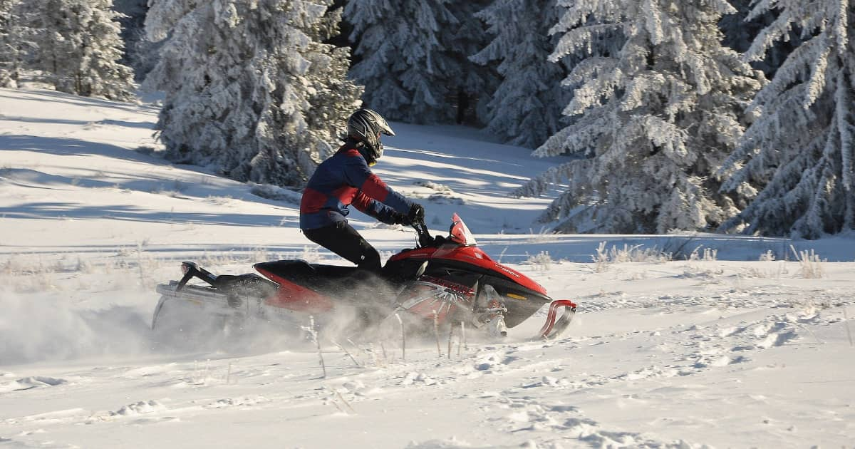 Snowmobiler riding across the snow in the forest