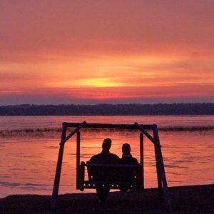 Couple on a swing by Leech Lake at sunrise
